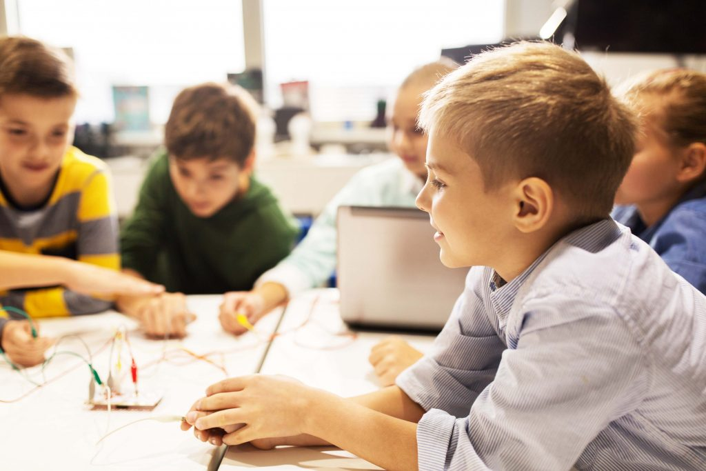 Bambino sorride a scuola mentre gioca con i suoi amici